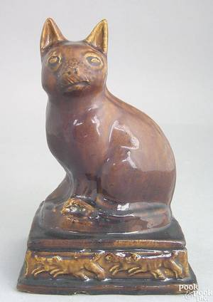 Earthenware figure of a recumbent cat resting on a plinth mid 19th c