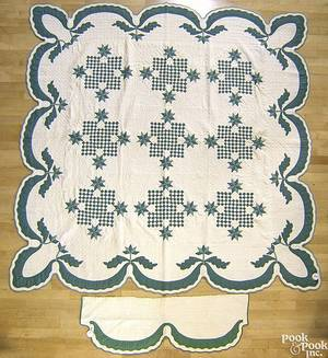 Green and white pieced quilt with scalloped border