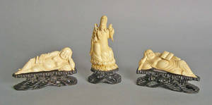 Two carved ivory reclining Buddhas on teak stand