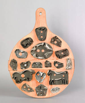 Mounted group of eighteen tinned sheet iron cookie cutters 19th c