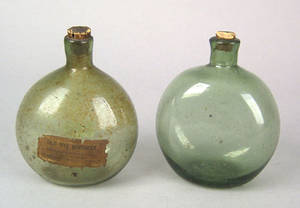 Three green blown glass squat spirit bottles early 19th c