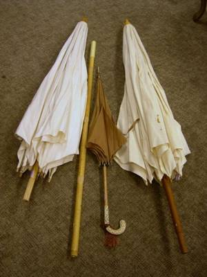 Two Early 20th Century Linen Beach Umbrellas and a Faux Ivory Handled Rain Parasol
