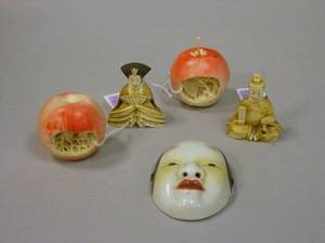Japanese Carved Ivory Emperor and Empress Figures a Small Porcelain Mask and a Pair of Chinese Carved Ivory Apples with Interior Land
