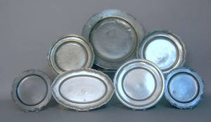 Seven pewter plates and chargers