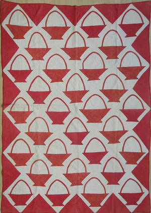 Red and white pieced quilt in a basket pattern