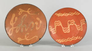 Two slip decorated redware plates 19th c