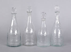 Four wheel engraved colorless glass decanters early 19th c
