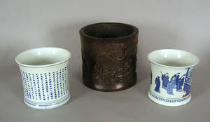 Two Chinese porcelain cache pots together with a carved wooden cache pot