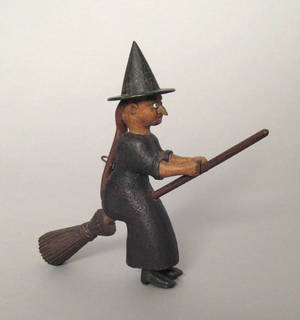 Carved and painted figure of a witch riding a broom late 19th c