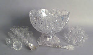 Cut glass punch bowl on stand with sterling ladle and associated punch cups