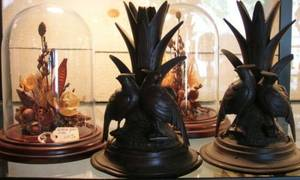 Pair of Victorianstyle Dried Flower Studies under Glass Domes and a Pair of Black Forest Carved Wood Figural Vases