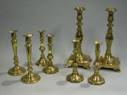 Four Pairs of Brass Candlesticks and a Pair of Cast Iron Figural Andirons