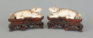 Two Chinese carved ivory foo dogs