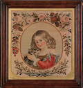 Woolwork picture of a young girl holding her cat in a floral border
