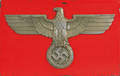 Large metal eagle and swastika on a red board background