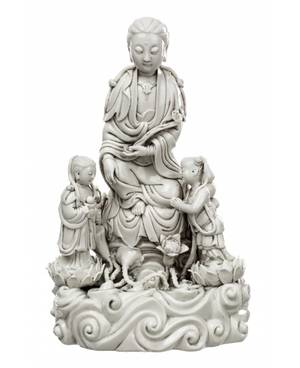 A BLANCDECHINE FIGURE OF GUANYIN ON A ROCK WITH TWO ATTENDANTS