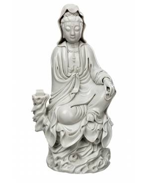 A BLANCDECHINE FIGURE OF GUANYIN ON A ROCK