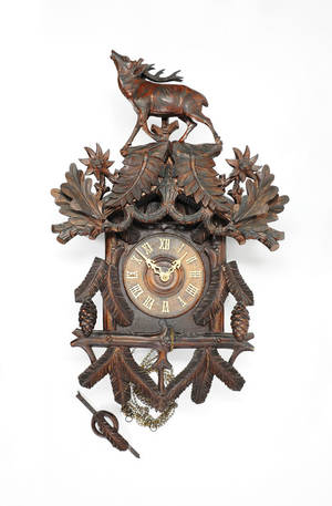Carved cuckoo clock with stag pediment and carved leaves and pine cones