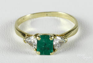18K yellow gold ring with a central rectangular cut emerald flanked by two triangular cut diamonds