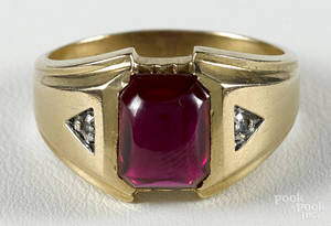 14K yellow gold ring with a central synthetic ruby cabochon flanked by two small diamond accents
