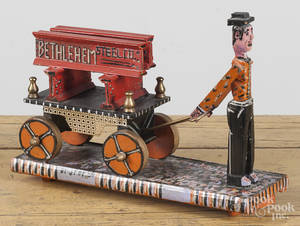 Contemporary carved and painted folk art figure pulling a cart of beams