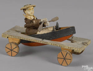 Painted pine and composition articulated boy in a row boat pull toy