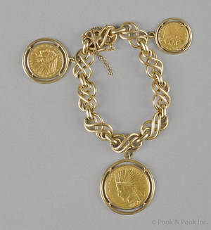 14K yellow gold charm bracelet with three gold coin charms including a 1915 US Liberty half dollar