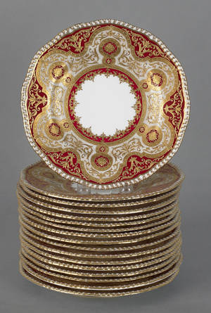 Seventeen Coalport porcelain plates with gilt decoration on a red ground