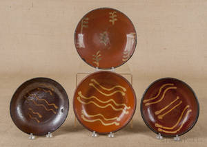 Four Pennsylvania slip decorated redware plates 19th c