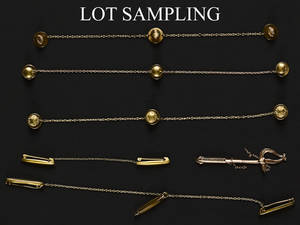 Eleven gold lingerie pin sets joined by chains