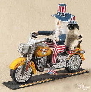 Carved and painted outsider art Uncle Sam riding a Harley Davidson motorcycle