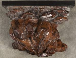 Black Forest carved wall shelf with a later ebonized top