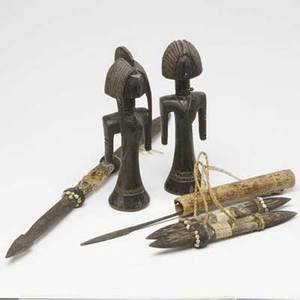 Tribal art two carved wood african figures together with four pacific island daggers 20thc largest 29