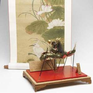 Asian papier mache and paper dragon held aloft by poles facing a flaming pearl with two wooden tablets with calligraphy in a fitted display case together with remounted scroll with cranes and lotus