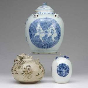 Chinese porcelain and stoneware three pieces two underglaze blue decorated a covered jar with foo dog head handles and medallions repaired and a small ovoid jar with phoenix medallions and dragon