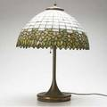 Lighting american glass and bronze table lamp the leaded geometric shade with floral border below a white ground unmarked 23 x 16