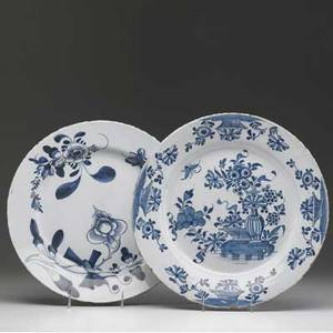 English delft two chargers one lambeth and one bristol both with floral decoration 18th c larger 13 12 dia