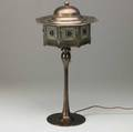 Jugendstil style copperpatinated brass table lamp its faceted shade with copper top and leaded glass panes on a candlestick base unmarked 24 x 11