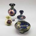 Moorcroft four items three pieces in the anemone pattern vase bowl candlestick single vase in hibiscus pattern on yellow ground all stamped moorcroft made in england blue ink signatures or s