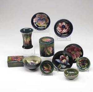 Moorcroft eleven pieces in assorted floral patterns two covered boxes in hibiscus and leaves and flowers one cabinet vase two small plates three small bowls three salts small fleck to one of t