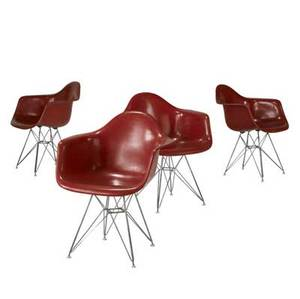 Charles and ray eames  herman miller set of four red fiberglass armchairs on eiffel tower bases embossed mark 30 34 x 25 x 18 12