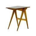 French side table with trapezoidal top covered in black laminate on compassshaped legs 22 x 17 34 x 17 34