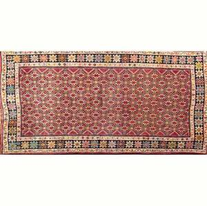 Northwest persian area rug with geometric field on a red ground surrounded by a geometric border 108 x 62