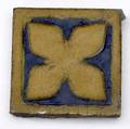 Grueby eighteen tiles with quatrefoil decoration in blue and yellow ochre some chips to edges each 4 sq