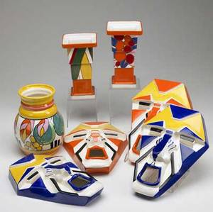 Collection of clarice cliff for wedgwood seven contemporary pieces includes vase with fruit design pair of geometric vases with square openings and two pairs of wallhanging masks with blue or oran