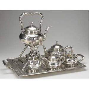 Chinese export silver tea service by zee wo shanghai ca 1900 seven pieces with bulbous bodies raised and chased moon and bamboo motifs bamboo handles spouts and finials rectangular tray 22