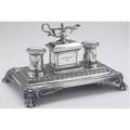 Victorian silver desk standish by e  j bernard london 1858 the central lidded chamber with serpenthandled lamp flanked by a pair of gadrooned inkwells on rectangular base with paw feet inscribe