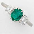 Emerald and diamond threestone platinum ring oval faceted emerald 56 ct flanked by two oval faceted diamonds approx 60 ct tw 42 gs gw size 6 34