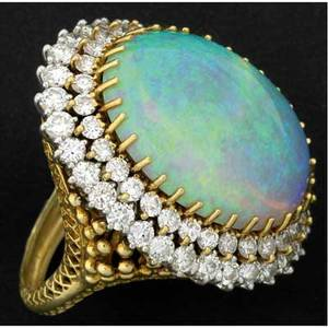 Large opal and diamond ring platinum and 18k yg with a very fine oval cabochon bluegreen opal approx 187 cts surrounded by two rows of circular brilliant cut diamonds approx 6 cts tw mid20t