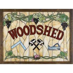Stained glass window with the word woodshed surrounded by grape clusters vines and various tools 20th c 44 x 58